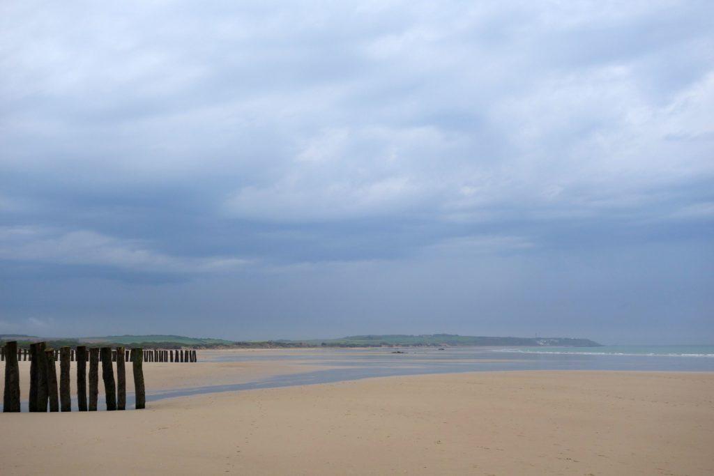 Ein breiter Strand am Meer. Links im Bild stehen Pfähle, die in den Sand eingelassen sind.
