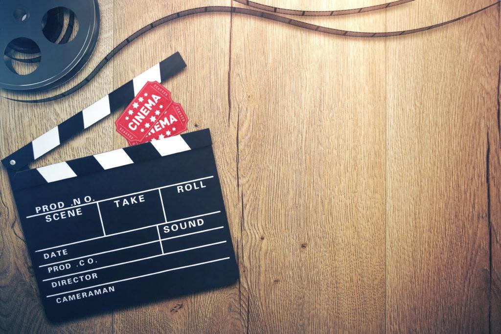 Filmklappe und Filmrolle auf Holztisch
