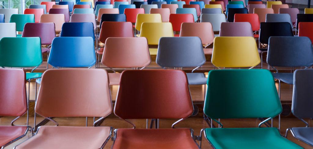 Reihen mit bunten Stühlen.